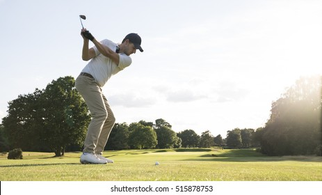 Man hitting golf shot on a golf course in the sun