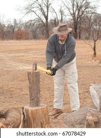 Man hitting a piece of wood with his ax, splitting it