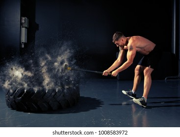 Man hitting wheel tire with hammer sledge. Cross-fit training