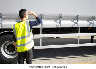 Man in hi-viz jacket carries out health and safety checks on an articulated lorry truck trailer