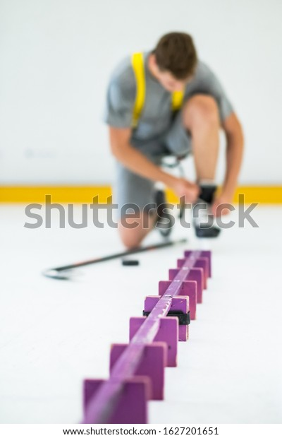 man with hockey stick and puck on ice
