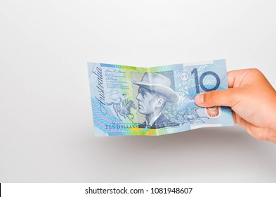 Man hold 10 Australian dollar Banknote on white background. Selective focus.