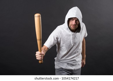Man hold baseball bat, aggression. Hooligan wear hood in hoody, fashion. Gangster guy threaten with bat weapon. Aggression, anger and violence concept.