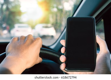 Man hold the car steering with using mobile phone during driving - Safety driving concept
