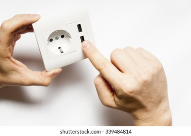 A man hold the electric socket with two usb-charger ports.