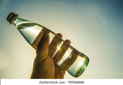 man hold full glass bottle in hand without label on blue sky with sun rays on background. sunlight. empty copy space for inscription. sun rays between fingers. white glass clear pour water in bottle