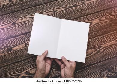 Man hold in hands open blank brochure. Top view