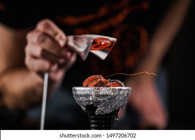A man hold the hot coal with a clamp above the shisha's bowl. Setting up a hookah