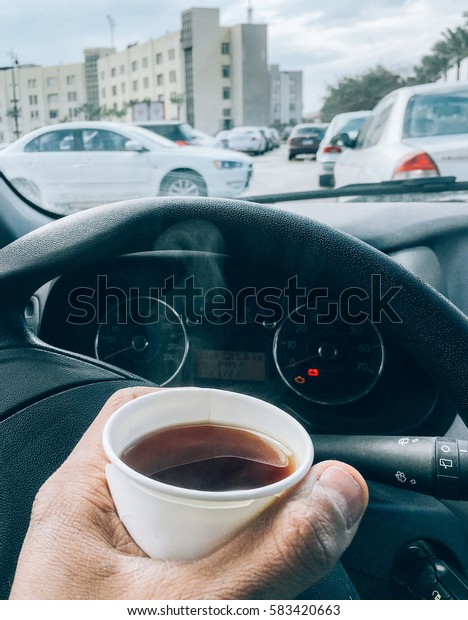 Man hold hot tea paper cup in car.