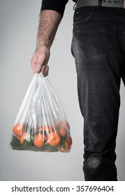 a man hold a plastic bag with tangerines