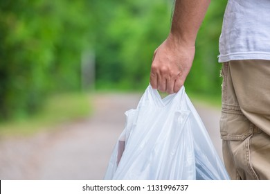Man hold the plastic bags and walk on the street in the park