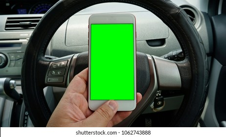 A man hold smartphone with green screen (Chroma key) with blurred Car dashboard background. Open conceptual for technology stuff.