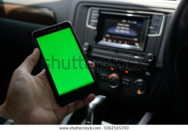 A man hold smartphone with green screen (Chroma key) with Car dashboard background. Open conceptual for technology stuff.