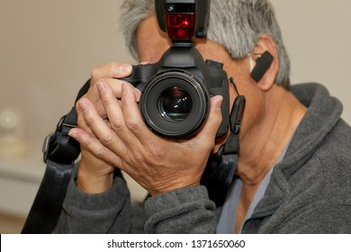 Man holding a 35mm digital SLR camera in preparation to take a photograph with shallow depth of field
