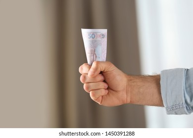 Man holding 50 Ukrainian Hryvnias banknote against blurred background, closeup with space for text. International relationships