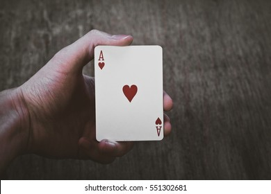 Man holding ace of hearts in hands isolated on wood background