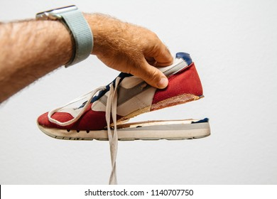 Man holding against white background one sport footwear sneaker with broken sole - quality manufacturing problems