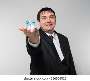 man holding an alarm clock in hands