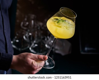 man holding an alcohol yellow cocktail