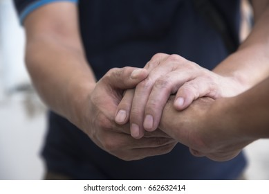 A man in holding another man's hand for sympathy
