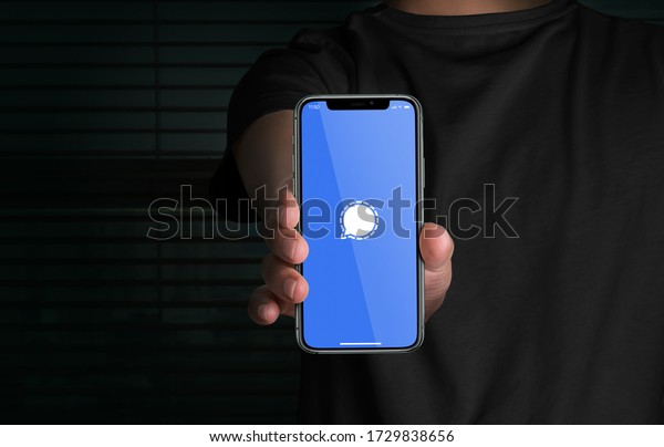 Man holding Apple iPhone 11 displaying Signal app logo. Social media network. Signal Messenger, LLC. Privacy focused app. Advanced privacy-preserving technology.