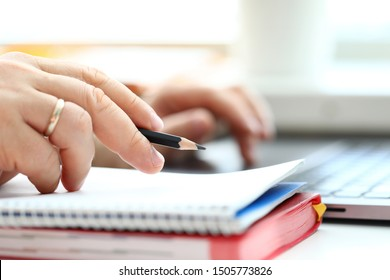 Man holding in arm regular lead pencil while typing something at laptop pc closeup