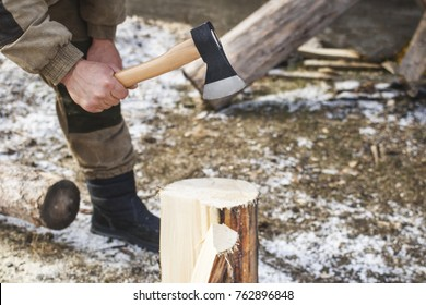 A man holding an axe and chopping wood