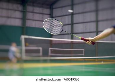Man holding badminton racket in badminton court.