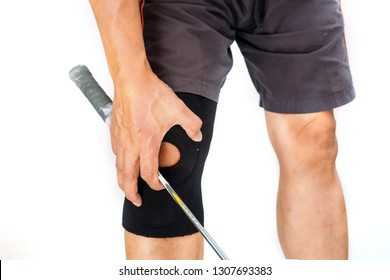 A man holding a badminton racquet clutching his knee with his hand in pain because of an injury on white background