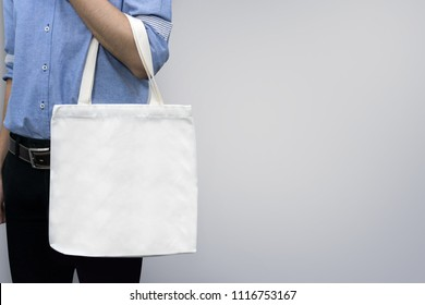 Man holding bag canvas fabric for mockup blank template on gray background.