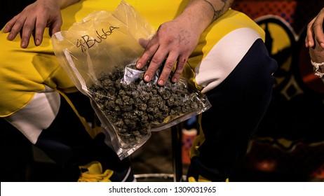 A man holding a bag of pre-98 Bubba Kush cannabis flowers.