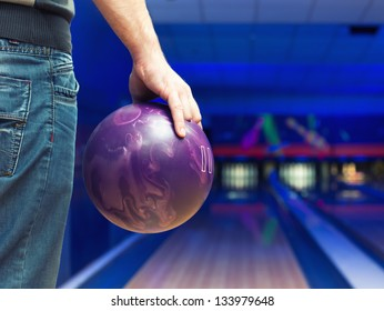 Man holding ball against bowling alley
