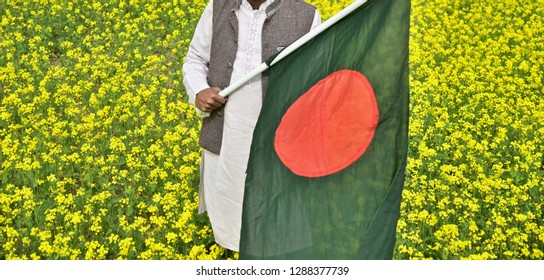 Man holding a Bangladeshi national flag standing in a mustard field