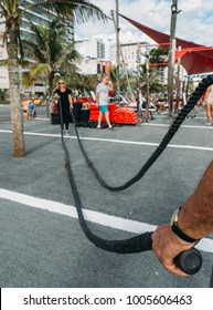 Man holding battling rope with older woman (70-79) on background at public gym in Ipanema, Rio de Janeiro, Brazil