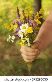 Man holding a beautiful bouquet of field flowers