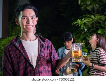 Man holding beer in barbecue party celebration. Asian men and woman enjoy food and drink.