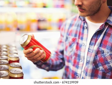 Man holding beer can in a liquor store, choosing beer