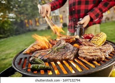 Mann, der ein Biergrillfleisch auf einem Grillplatz im Freien in seinem Garten hält und die Würstchen mit Zangen in einer Nahaufnahme auf die Rindsteaks, Corncob, Chilischoten und Hühnerbrust dreht