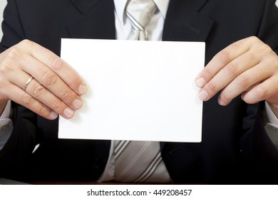 a man holding before him a blank sheet of paper