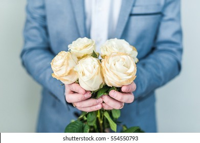 A man holding before him a bouquet of white roses. The guy covers his face with flowers. Valentine's day, international women's day, mother's day