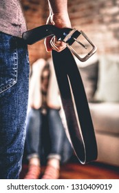 Man holding belt in hand for beating up his wife. Domestic violence and abuse.