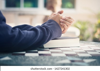 man holding a bible in her hands and praying