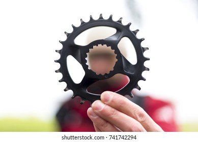 The man is holding a bicycle narrow wiade chainring in his hand. The man is blurred in the background.