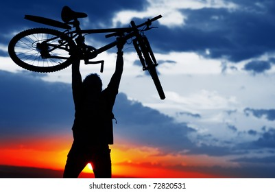 Man holding a bicycle over himself on sunset background