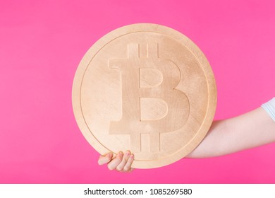 Man holding big bitcoin on pink background