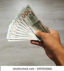 Man holding a big heap of one thousand dollars from United States. US dollars, the currency of USA with a table on the background. Payment and salary concept. 1000 USD in new notes of one hundred.