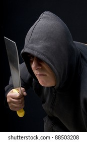 a man holding a big knife in black background in studio