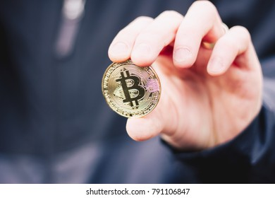 Man holding a bitcoin between his fingers