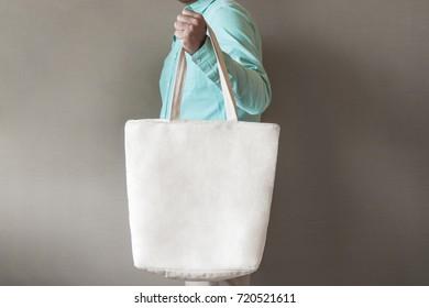 man holding black canvas tote bag mock up
