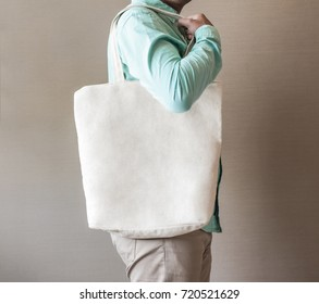 man holding black canvas tote bag mock up